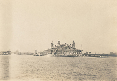nypl.digitalcollections.A view of Ellis Island taken from the harbor. At the center is the Immigration Station; one of the boats in the pier is the John E. Moore.(500)