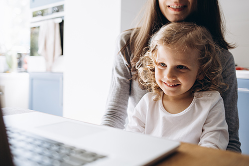 Young mother and her little daughter sitting using a laptop