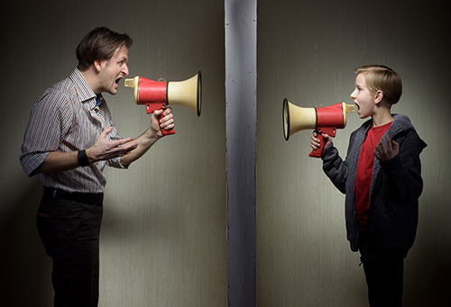 Tween son and his father yelling through the megaphones standing