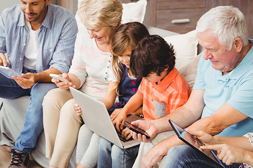 Family with grandparents using technology while sitting on sofa