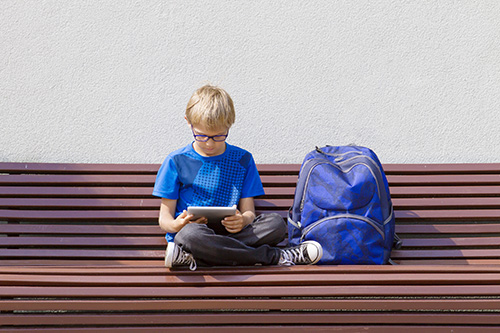 Boy with glasses using tablet PC. Child sitting on the bench. Outdoor. Free copy space. Education, technology, people concept